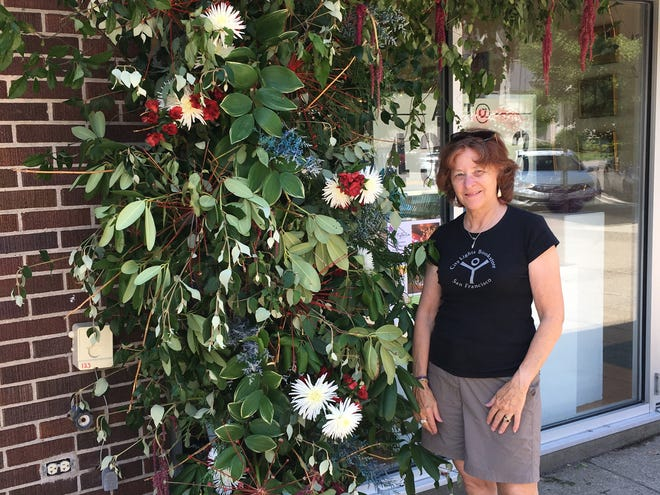 """Granville's Evelyn Frolking, """"eco-conscious floral artisan,"""" with her completed display."""