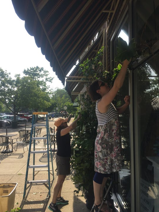 Evelyn Frolking and Susan Klemetti at work on the floral structure early Saturday morning, June 29.