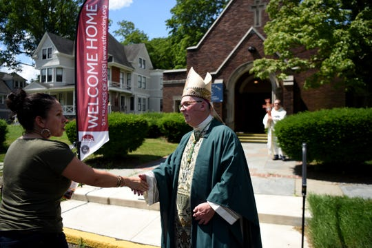 Rev. George Lucey welcomes a parishioner outside of  St. Francis of Assisi Church in Glen Ridge on June 30, 2019.