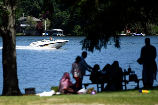 A man drives his boat on Lake Hopatcong as people picnic along the waterfront at Hopatcong State Park on Monday, July 1, 2019, in Landing, NJ. Due to the harmful algae bloom, swimming is not allowed in Lake Hopatcong until further notice.