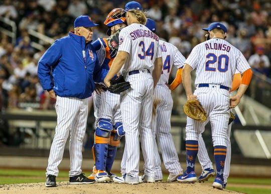 New York Mets pitching coach Phil Regan (58) meets with pitcher Noah Syndergaard (34) in the sixth inning against the Atlanta Braves at Citi Field.