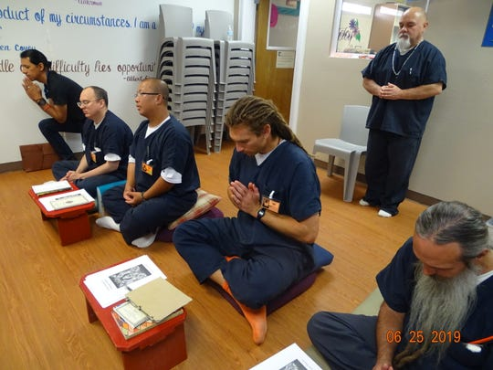 Otero County prison inmates pray during a Buddhist lecture at the Otero County Prison Facility Tuesday, June 25.