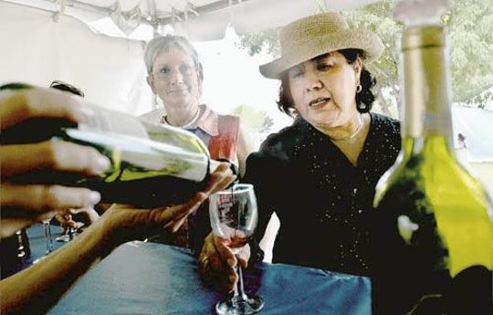 In this file photo, two Silver City Wine Festival goers enjoy a glass of wine