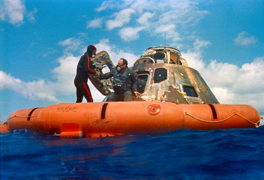 Astronaut Edgar D. Mitchell, lunar module pilot, is assisted out of the Command Module (CM) by a U.S. Navy underwater demolition team swimmer during the 1971, Apollo 14 recovery operations in the South Pacific Ocean.