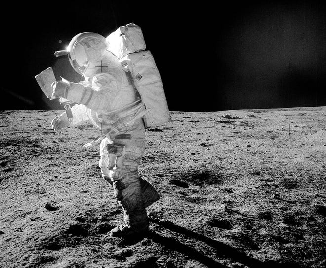Edgar Mitchell moves across the lunar surface as he looks over a traverse map during exploration of Fra Mauro. Lunar dust can be seen clinging to the boots and legs of the space suit during the 1971 Apollo 14 mission.