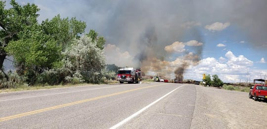 San Juan County Fire Department is battling the 7-acre Arroyo Fire, which has burned several buildings and vehicles.