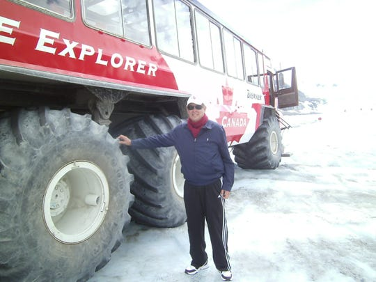 """It's almost as tall as I am!"" Glacier visitor Ron Hagquist of Alto marvels at the massive tires of the Ice Explorer vehicle."