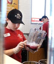 Kaitlyn Rhon prepares a Smoothie King beverage for the blender.