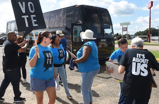 Jennifer Harding brings out aa VOTE sign after exiting the Black Voters Matter bus tour in Lafayette Monday.