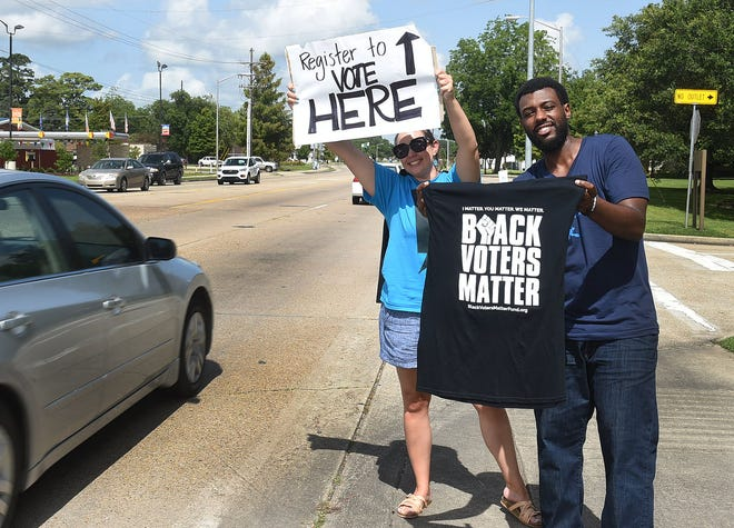 Jennifer Harding and Anza Becnel draw attention to motorist on Willow Street as they volunteer their time on the Black Voters Matter bus tour that arrived in Lafayette Monday to register voters.