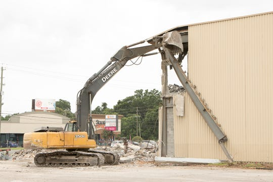 Demolition of the former Sears Auto Center building on North Davis Highway continues Monday.
