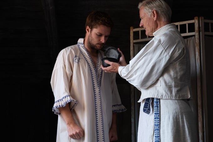 "Mats (Lennart R. Svensson) helps Christian (Jack Reynor) prepare for a solstice ceremony in ""Midsommar."""