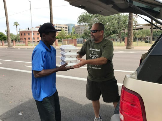 Alexi Devilliers (right) passes out lunches on June 30, 2019. He makes lunch every weekend for 100 homeless people.