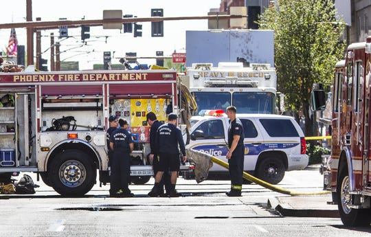 Police, firefighters and employees of APS investigate the scene of an underground explosion at Second Avenue and Washington Street in Phoenix on July 1, 2019.