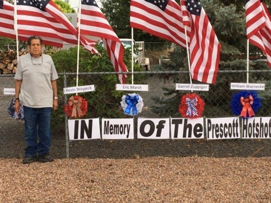 "Ernie Ortega, 74, stands next to a sign that reads ""In Memory Of The Prescott Hotshots"" in a memorial he created in his front yard. He hopes people remember the hotshots who died during the Yarnell Hill Fire."