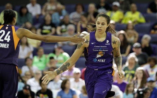 Phoenix Mercury's Brittney Griner, right, gets a high five from teammate DeWanna Bonner as they head to the sideline for a timeout against the Seattle Storm in the second half of a WNBA basketball game Sunday, June 30, 2019, in Seattle. The Mercury won 69-67.