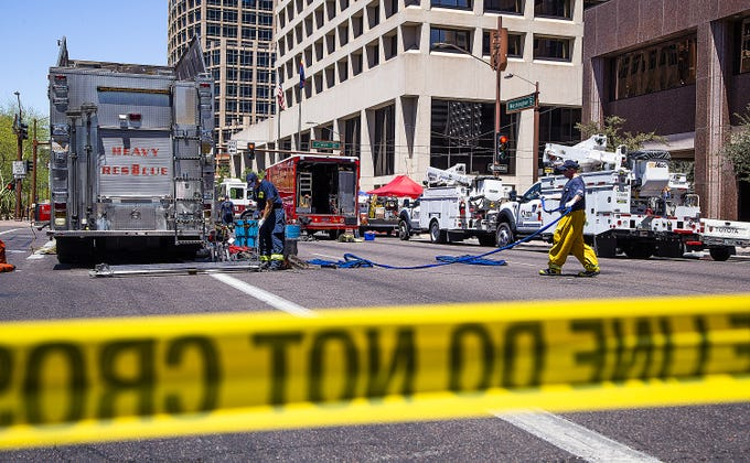 Police, firefighters and employees of APS investigate the scene of an underground explosion at First Avenue and Washington Street in Phoenix on July 1, 2019.