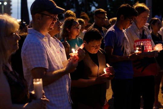 Personas portan velas en honor a Óscar Alberto Martínez y su hija Valeria, que fueron sepultados en El Salvador.