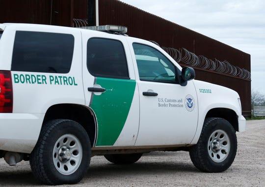 Un agente de la Patrulla Fronteriza de los Estados Unidos atraviesa una puerta en la cerca a lo largo del río Grande cerca de McAllen, Texas.