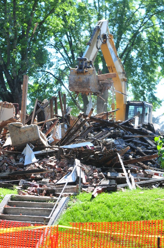 Rubble is lifted off a pile Monday, July 1, 2019, during demolition of a North 11th Street building burned by fire.