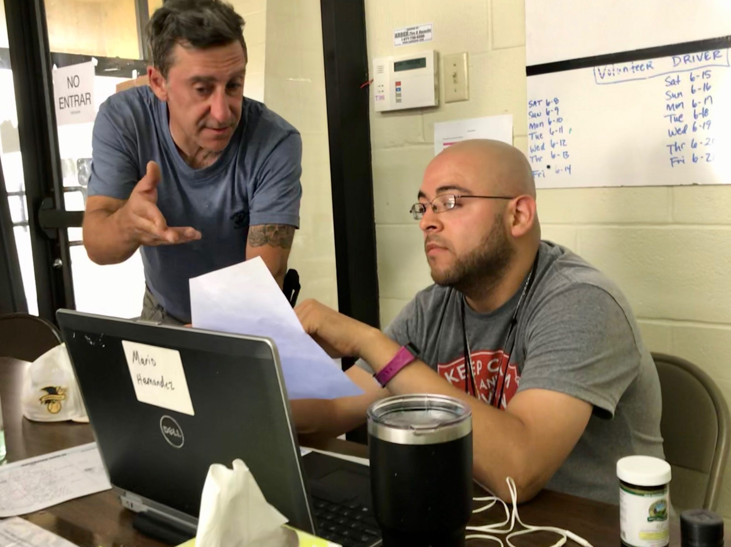 Volunteers Paul Acres (Left) and Mario Hernandez (Right) review documents to help arrange travel for migrant families arriving at the Val Verde Border Humanitarian Coalition Center in Del Rio, Texas. June 19, 2019.