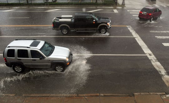 Cars drive through pooling water during a storm Monday, July 1, on Minnesota Ave. in Sioux Falls.