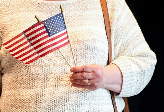 Senate candidate Scyller Borglum's mother, Susan Borglum, holds small American Flags at her daughter's candidacy announcement Monday, July 1, at the Hilton Garden Inn in Sioux Falls.