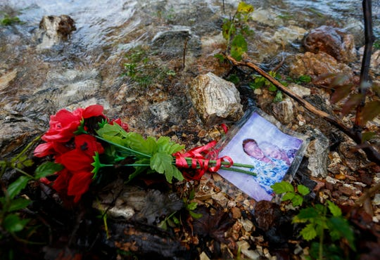 A photo of William Asher, 69, and Rosemarie Hamann, 68, lay next to a bouquet of artificial flowers on the shoreline of Table Rock Lake on Wednesday, June 26, 2019 near where Stretch Duck 7 sank, killing 17 people on July 19th of last year.