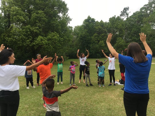 Youth Health Leadership members lead the South City children in some warm-up exercises.
