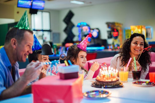 Young siblings celebrating birthday with their parents in the bowling center.