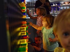 A group of children play with a light board at the Children's Museum of the Upstate in Greenville.