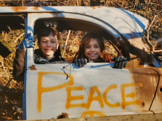 Dylan and Sophia Lebowitz pose for photos in a a  rusted out relic in Graham Hills Park.