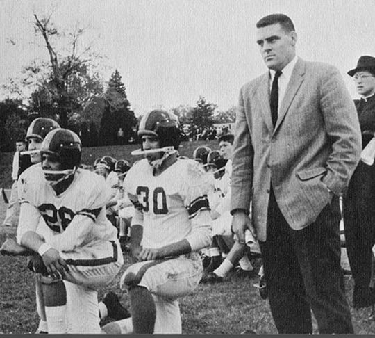 A young Joe Biden (30) crouches beside Archmere Academy football coach John Walsh in 1960.