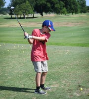 Ryan Johnson practices his swing while attending Brownie's Golf Clinic, coached by golf pro Craig Brown at the Champions Course at Weeks Park.