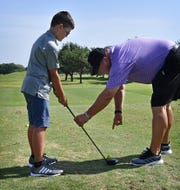 Riley Cunningham gets a few pointers from PGA golf pro Craig Brown during a youth golf clinic at the Champions Course at Weeks Park.