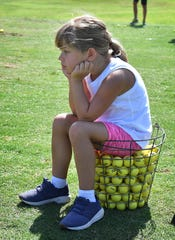 Caroline Cole watches and waits her turn during a youth golf clinic at the Champions Course at Weeks Park.