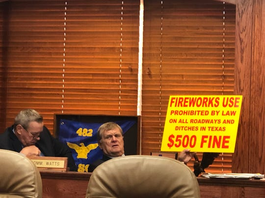 Wichita County Commissioner Barry Mahler holds up one of the signs Monday that county crews will be placing along public roads to remind people that it is illegal to shoot off fireworks from roadways or ditches. A fireworks violation could result in an up to $500 fine.