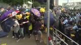 Police in Hong Kong use pepper spray and batons against anti-government protesters who had seized highways early Monday.