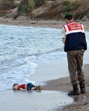 A Turkish police officer stands near the washed up body of refugee child Alan Kurdi, who drowned during a failed attempt to sail to the Greek island of Kos, on Sept. 2, 2015.