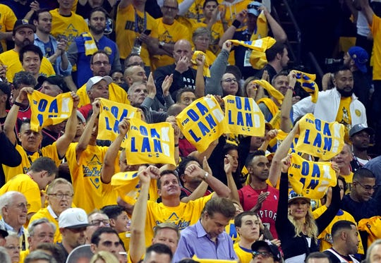 Fans wave towels with a dedication to injured player Kevin Durant during Game 6 of the NBA Finals.
