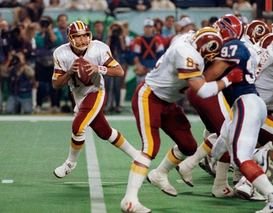 FILE - In this Jan. 26, 1992, file photo, Washington Redskins' Don Warren (85) keeps Buffalo Bills Cornelius Bennet (97) away from Redskins quarterback Mark Rypien during Super Bowl XXVI in Minneapolis. Rypien passed for 292 yards and two touchdowns to lead the Redskins to their third Super Bowl title.