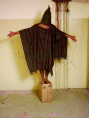 This is an image obtained by The Associated Press which shows an unidentified detainee standing on a box with a bag on his head and wires attached to him in late 2003 at the Abu Ghraib prison in Baghdad, Iraq.