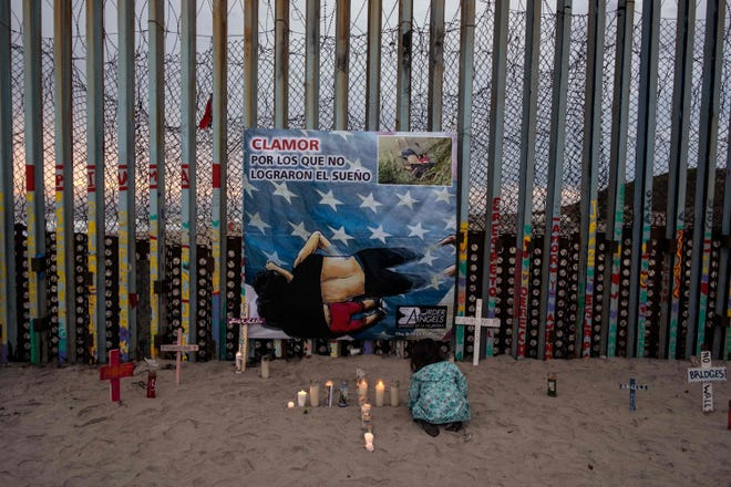"""A girl lights candles next to a poster with a painting of Óscar Alberto Martínez Ramírez and Valeria, hung for an event called """"Clamor for those who didn't achieve the dream"""" at the U.S.-Mexico border in Playas de Tijuana, Baja California state, on June 29, 2019, Mexico."""