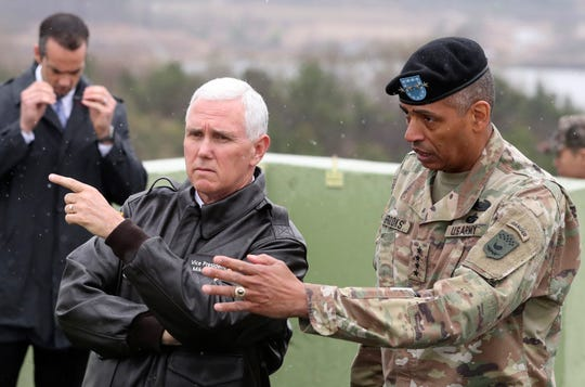 U.S. Vice President Mike Pence, left, is briefed by U.S. Gen. Vincent Brooks, right in the Demilitarized Zone (DMZ), near the border village of Panmunjom, South Korea, Monday, April 17, 2017.