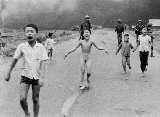 In this June 8, 1972, file photo, South Vietnamese forces follow after terrified children, including 9-year-old Kim Phuc, center, as they run down Route 1 near Trang Bang after an aerial napalm attack on suspected Viet Cong hiding places. (Photo: Nick Ut, AP)