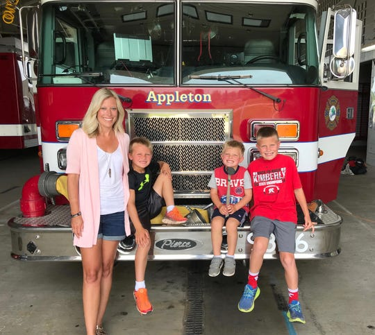 Lindsey Lundgaard with her three children, from left, Logan, Ryan and Evan. Lindsey's husband, Appleton firefighter Mitch Lundgaard, died May 15 in a shooting at the city's downtown transit center.
