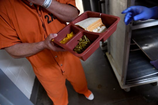 An inmate receives his tray of food during lunch.