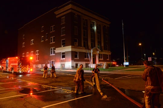 Battle Creek firefighters begin picking up hose outside the Masonic Center following a Tuesday morning fire.