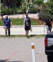 Three unidentified men were spotted Wednesday by Melbourne Beach police walking with AR-15s and fishing poles.