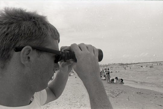 Lifeguard Mark Schwartz keeps an eye on swimmers at Corpus Christi's McGee Beach during the holiday on July 4, 1965.